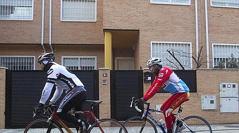 Due cicloamatori passano davanti alla casa di Contador