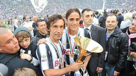 Andrea Pirlo e Alessandro Matri col trofeo che spetta ai vincitori dello scudetto. Ansa