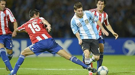 Inarrestabile: Leo Messi sfugge fra tre difensori paraguaiani. Afp