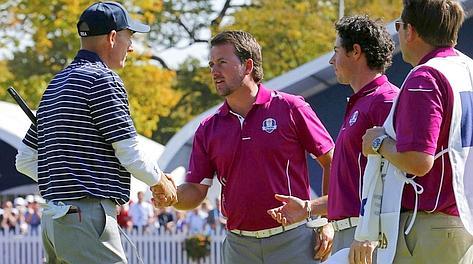 Jim Furyk a sinistra  saluta Graeme McDowell e Rory McIlroy alla fine della loro sfida. Reuters