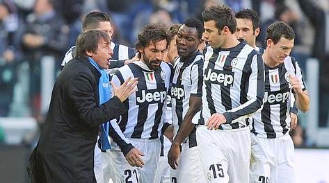 Conte e i compagni abbracciano Pirlo dopo la punizione del 2-0. Ansa