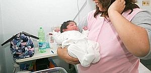 Una madre culla il suo neonato. Ansa