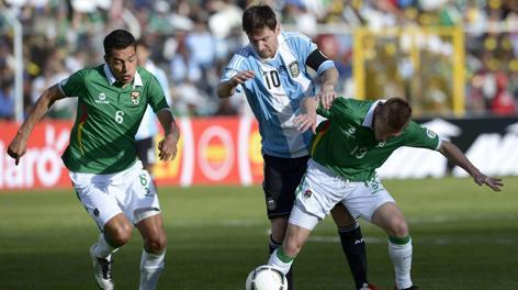 Leo Messi braccato da due difensori boliviani. Afp