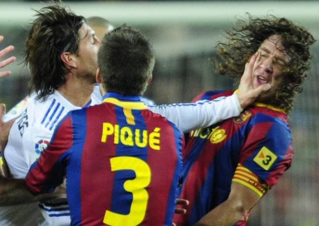 Subito dopo Sergio Ramos perde la testa: prima si fa espellere per un calcione a Messi, poi, uscendo, rifila questa manata a Puyol. Ap