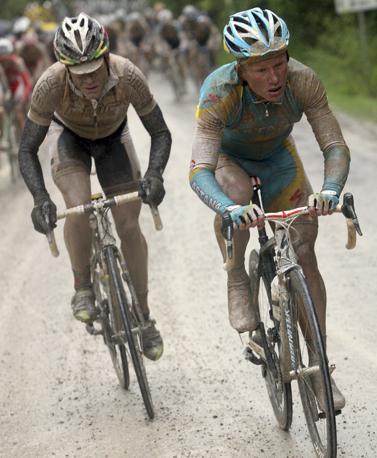Vinokourov e Evans coperti di fango. Bettini