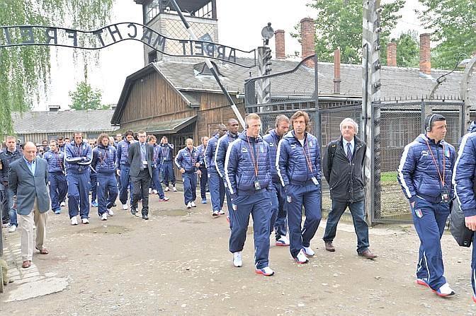"""La delegazione azzurra, accompagnata da alcuni ebrei reduci dei campi di concentramento, visita il Museo di Auschwitz, in Polonia. Ecco gli azzurri sotto la famosa scritta posta all'ingresso: """"Il lavoro rende liberi"""". Afp"""