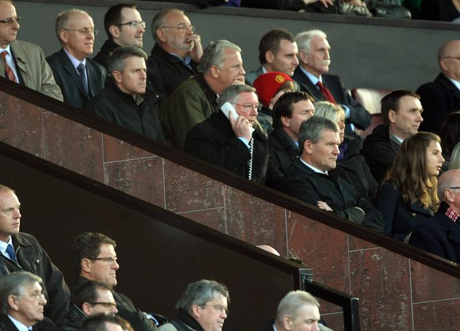 19 marzo 2011. Ferguson al telefono all'Old Trafford. In basso Fabio Capello. Ansa