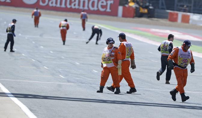 Decine di commissari intenti a ripulire la pista piena di detriti degli pneumatici. Reuters