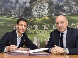 Rolando Mandragora firma il contratto con la Juve: accanto a lui Beppe Marotta. juventus.com