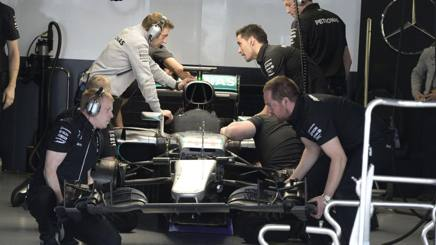 Meccanici e tecnici al lavoro al box Mercedes. Colombo