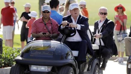 Donald Trump guida una golf cart nel suo Doral resort. Ap