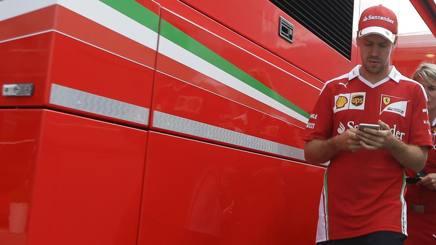 Il pilota Sebastian Vettel,29 anni, guarda il telefono nel paddock Ferrari sul tracciato del GP d'Ungheria. Ap