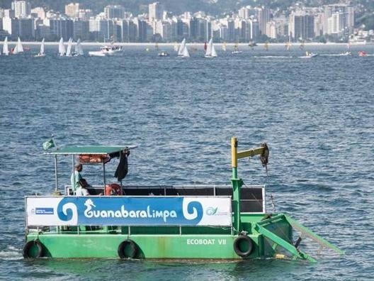 Eco Boat al lavoro nella baia di Rio, con velisti sullo sfondo