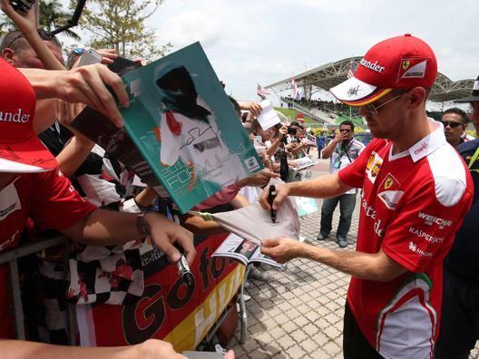 Sebastian Vettel firma autografi a Sepang. Lapresse