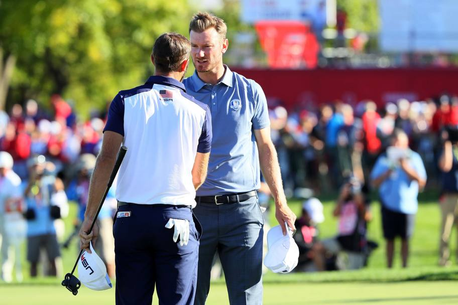 Lo statunitense Dustin Johnson stringe la mano a Chris Wood (Afp)