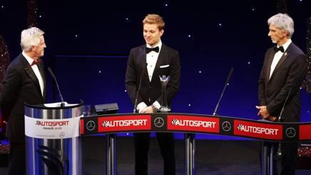 Rosberg (al centro) premiato da Damon Hill (a des), gli unici due iridati figli di iridati
