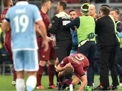 Un momento della risa scoppiata durante Lazio-Roma con Strootman che si lascia andare a terra. Afp