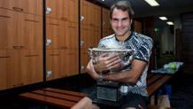 Roger Federer abbraccia il trofeo vinto a Melbourne. Afp