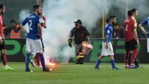 Un petardo  lanciato dal settore dei tifosi albanesi e raccolto da un vigile del fuoco. Ansa