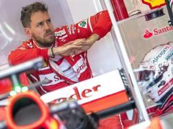 Sebastian Vettel concentrato ai box della Ferrari. Epa