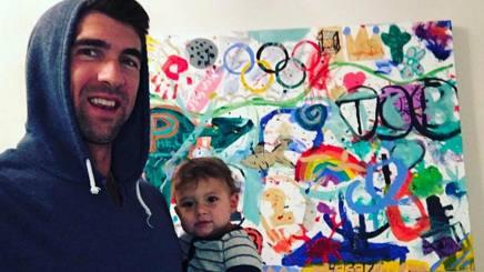Michael Phelps con il figlio Boomer davanti ad un quadro a tema olimpico, realizzato in famiglia