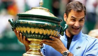 La curiosa espressione di Roger Federer, 35 anni, con il trofeo di Halle. Epa