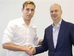 Lucas Biglia stringe la mano a Marco Fassone. Oggi è ufficialmente un giocatore del Milan.