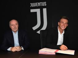 Bernardeschi firma il contratto con la Juventus, davanti all'a.d. bianconero Marotta. Getty Images