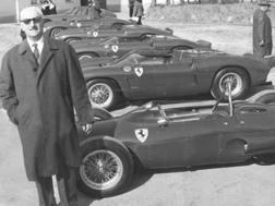 Enzo Ferrari in posa davanti alle sue vetture.