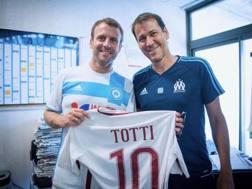 Il Presidente della Francia Macron con il tecnico del Marsiglia Garcia e la maglia di Totti.