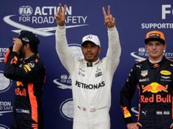 Lewis Hamilton esulta tra i due della Red Bull. Reuters