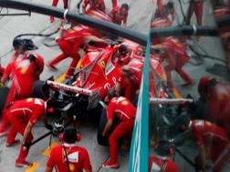 Meccanici Ferrari al lavoro ai box. Reuters