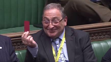 John McNally, del partito Scottish National, mostra il rosso a Theresa May che sta difendendo il suo parlamentare.