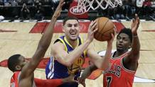Klay Thompson in penetrazione fra Kris Dunn e Justin Holiday (Ap)
