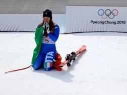 Sofia Goggia in ginocchio davanti al podio olimpico. Getty