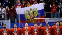La nazionale russa canta l'inno sul podio, mentre alle spalle i tifosi sventolano la bandiera