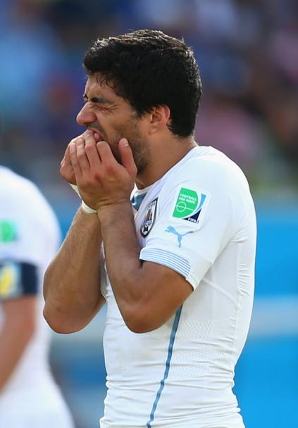 Suarez prosegue, senza vergogna, a tenersi i denti in segno di dolore (Getty Images)