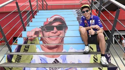 Valentino Rossi sulla scala con la sua effige nel paddock argentino. Milagro