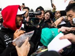 Lewis Hamilton firma autografi in Cina. Afp