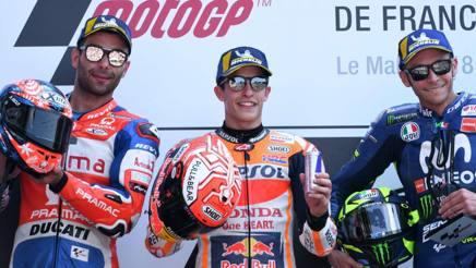 Marc Marquez esulta per la vittoria di Le Mans tra Petrucci e Rossi. Afp