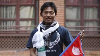 L'alpinisista nipponico Nobukazu Kuriki con la bandiera nepalese. Ap