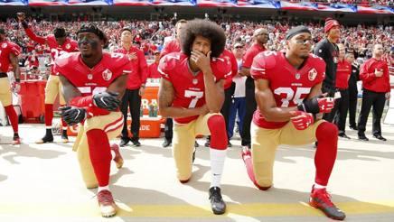 Colin Kaepernick, al centro, qb dei San Francisco 49ers, protesta inginocchiato contro l'inno EPA