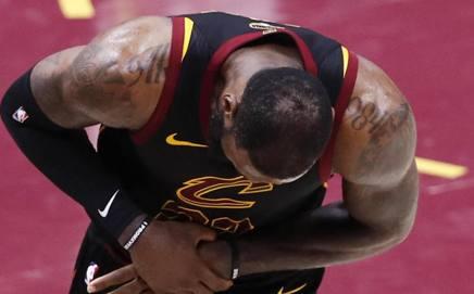 LeBron James, 33 anni, chinato si tiene la mano destra sofferente: è il segno della resa EPA