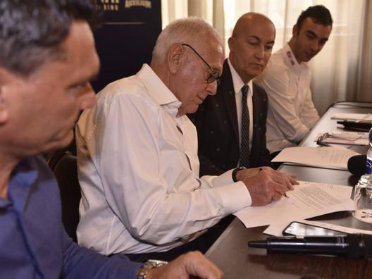 Coach Larry Brown, 77 anni, mentre appone la sua firma sul contratto che lo lega all'Auxilium Torino CIAM