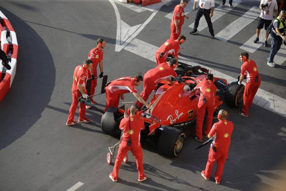 I meccanici Ferrari spingono ai box la Ferrari incidentata. Ap