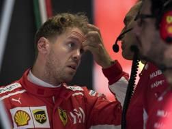 Sebastian Vettel a colloquio con i tecnici Ferrari. Ap