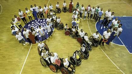 """Il logo Oso del progetto """"Sport per Tutti"""" con un gruppo di persone della Fondazione Santa Lucia"""