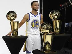 Steph Curry, 30 anni, coi tre Larry O'Brien Trophy vinti coi Warriors. Epa