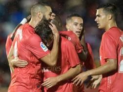 Karim Benzema festeggiato dai compagni dopo il vantaggio del Real. Afp