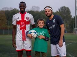Un giocatore del St. Ambroeus, con un piccolo calciatore e Eddy Veerus, de